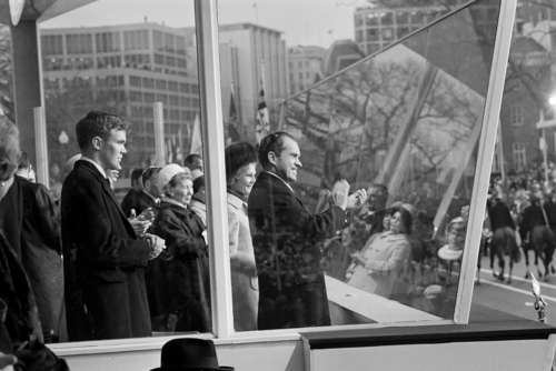President Nixon applauds a passing unit during the inaugural parade in Washington, D.C., Jan. 20, 1969. He stands behind bullet proof glass with his wife Pat Nixon by his side. Former first lady Mamie Eisenhower, stands at Mrs. Nixon's left. (AP Photo)