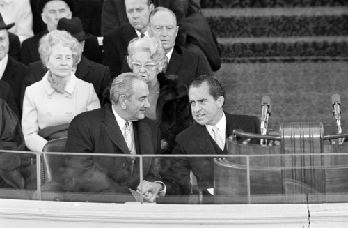 President Nixon and former President Lyndon B. Johnson clasp hands as they sit on the inaugural stand where Nixon took the Oath of Office as chief executive, in Washington, D.C., Jan. 20, 1969. (AP Photo/Preston Stroup)