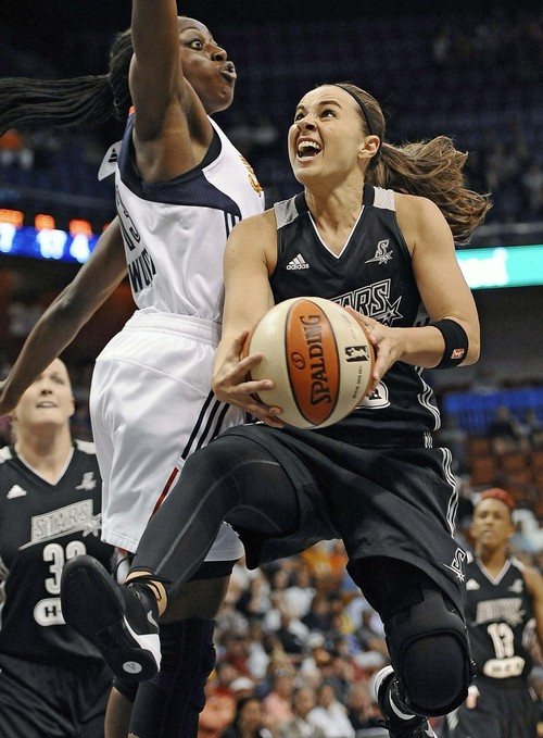 FILE - In this July 1, 2014 file photo, San Antonio Stars' Becky Hammon, right, drives to the basket as Connecticut Sun's Chiney Ogwumike, left, defends during the second half of a WNBA basketball game in Uncasville, Conn. (AP Photo/Jessica Hill, File)