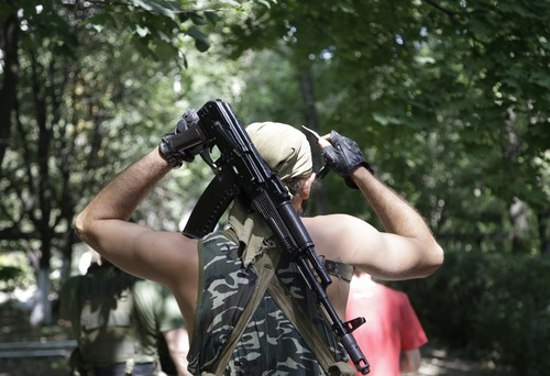A Pro-Russian rebel adjusts his weapon in Donetsk, eastern Ukraine, Wednesday, Aug. 6, 2014. Air strikes and artillery fire between pro-Russian separatists and Ukrainian troops in the eastern city of Donetsk have brought the violence closer than ever to the city center, as Kiev's forces move in on the rebel stronghold. (AP Photo/Sergei Grits)