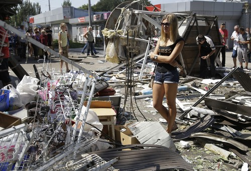 Residents inspect the damage after night shelling on a market in Donetsk, eastern Ukraine, Wednesday, Aug. 6, 2014. Airstrikes and artillery fire between pro-Russian separatists and Ukrainian troops have brought the violence closer than ever to the city center, as Kiev's forces move in on the rebel stronghold. (AP Photo/Sergei Grits)