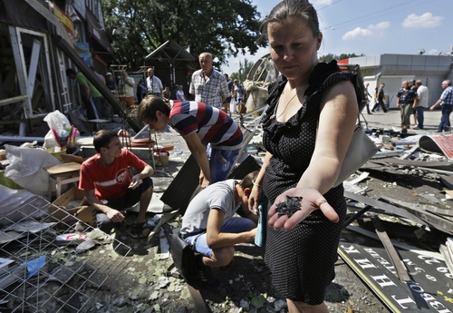 A local woman collects fragments of a shell, after night shelling on a local market, in Donetsk, eastern Ukraine, Wednesday, Aug. 6, 2014. Air strikes and artillery fire between pro-Russian separatists and Ukrainian troops in the eastern city of Donetsk have brought the violence closer than ever to the city center, as Kiev's forces move in on the rebel stronghold. (AP Photo/Sergei Grits)