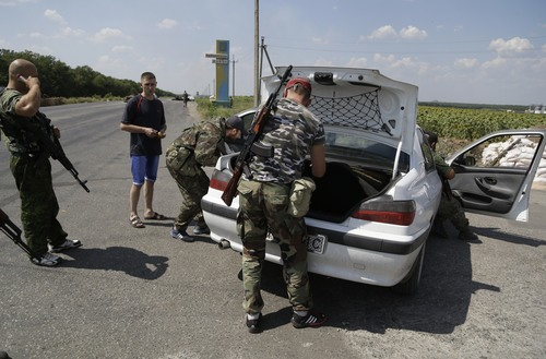 Pro-Russian rebels search the car of a local resident at a checkpoint near the city of Donetsk, eastern Ukraine, Wednesday, Aug. 6, 2014. Air strikes and artillery fire between pro-Russian separatists and Ukrainian troops in the eastern city of Donetsk have brought the violence closer than ever to the city center, as Kiev's forces move in on the rebel stronghold. (AP Photo/Sergei Grits)