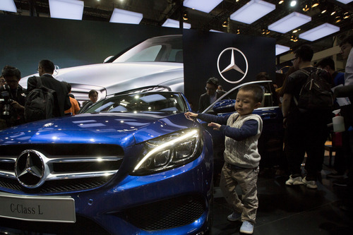 In this photo taken Sunday, April 20, 2014, a child touches the latest model from Mercedes at an auto show in Beijing, China. Chinese regulators have launched a series of anti-monopoly investigations of foreign automakers and technology providers, stepping up pressure on foreign companies that feel increasingly unwelcome in China. On Wednesday, a regulator said Chrysler and Germany's Audi will be punished for violating anti-monopoly rules. Mercedes Benz and Japanese companies also are under scrutiny. (AP Photo/Ng Han Guan)