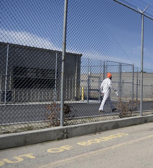 Al Hartmann  |  The Salt Lake Tribune  Inmate walks to his job along fenced pathway at the Utah State Prison in Draper.