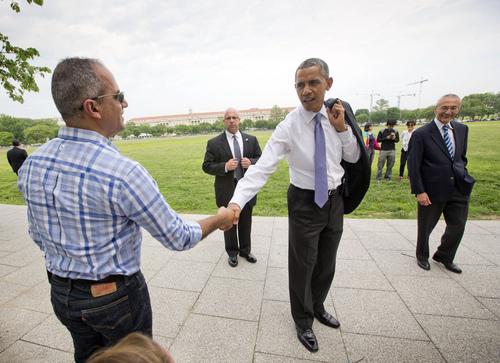 President Barack Obama, center, stops to greet a tourist during his walk with White House counselor John Podesta, right, to the Dept. of Interior, Wednesday, May 21, 2014 in Washington. Obama and Podesta also walked back to the White House after a signing a proclamation regarding the Organ Mountains-Desert Peaks National Monument. (AP Photo/Pablo Martinez Monsivais)