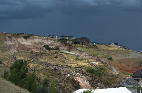 Steve Griffin  |  The Salt Lake Tribune   Dark skies loom behind a North Salt Lake City, Utah neighborhood where heavy rains caused the mountain side to slide destroying a home Tuesday, August 5, 2014.