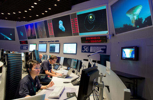 Experts watch their screens at the control center of the European Space Agency, ESA, in Darmstadt, Germany, Wednesday, Aug. 6, 2014. A mission to land the first space probe on a comet reaches a major milestone when the unmanned Rosetta spacecraft finally catches up with its quarry on Wednesday. It's a hotly anticipated rendezvous: Rosetta flew into space more than a decade ago and had to perform a series of complex maneuvers to gain enough speed to chase down comet 67P/Churyumov-Gerasimenko on its orbit around the sun. (AP Photo/dpa, Boris Roessler)