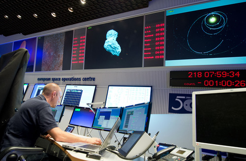 An expert watches his screens at the control center of the European Space Agency, ESA, in Darmstadt, Germany, Wednesday, Aug. 6, 2014. A mission to land the first space probe on a comet reaches a major milestone when the unmanned Rosetta spacecraft finally catches up with its quarry on Wednesday. It's a hotly anticipated rendezvous: Rosetta flew into space more than a decade ago and had to perform a series of complex maneuvers to gain enough speed to chase down comet 67P/Churyumov-Gerasimenko on its orbit around the sun. (AP Photo/dpa, Boris Roessler)