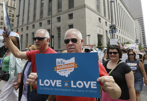 Gay marriage supporters march from the Potter Stewart United States Courthouse, rear, Wednesday, Aug. 6, 2014, to Fountain Square in Cincinnati. Three judges of the 6th U.S. Circuit Court of Appeals in Cincinnati are set to hear arguments Wednesday in six gay marriage fights from four states, Kentucky, Michigan, Ohio and Tennessee. (AP Photo/Al Behrman)