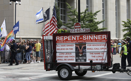 An anti-gay marriage supporters pulls a trailer saying 'Repent Sinner' past the Potter Stewart United States Courthouse where several hundred gay marriage supporters were picketing, Wednesday, Aug. 6, 2014, in Cincinnati. Three judges of the 6th U.S. Circuit Court of Appeals in Cincinnati are set to hear arguments Wednesday in six gay marriage fights from four states, Kentucky, Michigan, Ohio and Tennessee. (AP Photo/Al Behrman)
