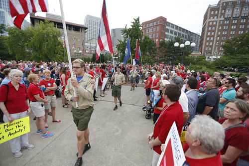 Color guard and members of the Cincinnati Chapter of Scouts for Equality march through the crowd for the National Anthem at a rally led by the group Why Marriage Matters Ohio in support of gay marriage in Lytle Park, Tuesday, Aug. 5, 2014 in Cincinnati. Federal appeals courts soon will hear arguments in gay marriage fights from nine states, part of a slew of cases putting pressure on the U.S. Supreme Court to issue a final verdict. (AP Photo/The Cincinnati Enquirer, Jeff Swinger)