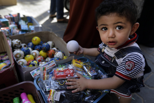 A Palestinian child goes through toys at a vendor's stall in a market in Gaza City, northern Gaza Strip, Wednesday, Aug. 6, 2014. A cease-fire between Israel and Hamas that ended a month of fighting is holding for a second day, ahead of negotiations in Cairo on a long-term truce and a broader deal for the war-ravaged Gaza Strip. (AP Photo/Lefteris Pitarakis)