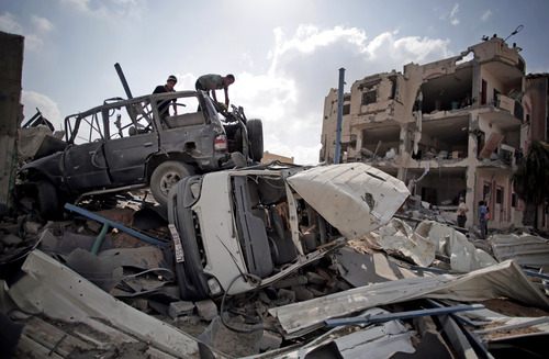 Palestinians search destroyed cars in Rafah's district of Shawkah in the southern Gaza Strip, Tuesday, Aug. 5, 2014. The attack at the Shawkah district east of the Gaza town of Rafah drew what was by far the heaviest shelling by the Israeli military in the Gaza war, killing nearly 100 people that day alone and instantly unraveling a three-day ceasefire shortly after it came into force. (AP Photo/Khalil Hamra)