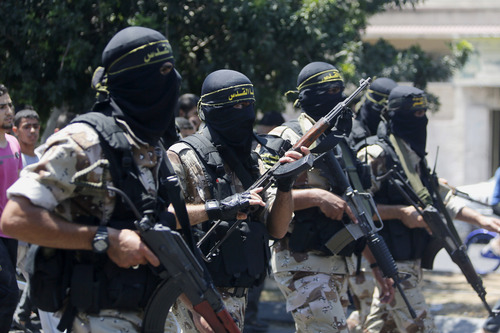 Masked militants of Islamic Jihad march during the funeral of Islamic Jihad militant Shaaban Al-Dahdouh, whose body was found under the rubble Tuesday, in Gaza City on Wednesday, Aug. 6, 2014. (AP Photo/Hatem Moussa)