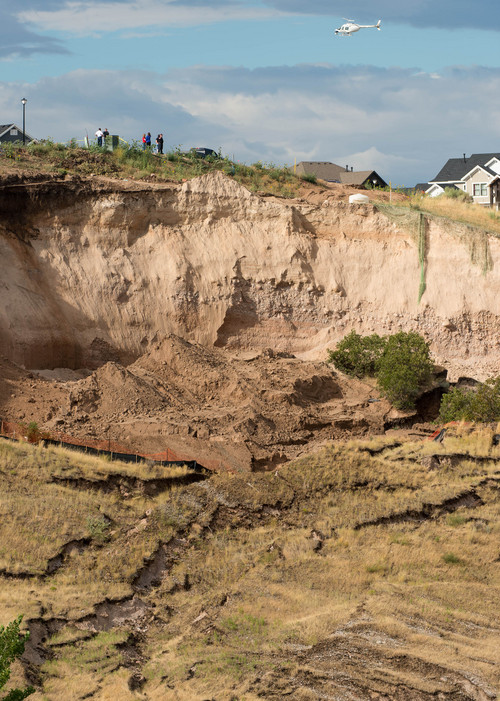 Trent Nelson  |  The Salt Lake Tribune A helicopter and onlookers take in the scene of a large landslide in North Salt Lake that destroyed one home and caused the evacuation of dozens more, Tuesday August 5, 2014.