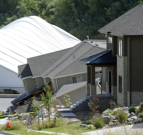 Al Hartmann  |  The Salt Lake Tribune  A home destroyed by a  landslide at Parkway Drive in North Salt Lake. Rubble from the landslide buckles the backside of the Eagleridge Tennis dome next door.  Residents returned to their homes Wednesday Aug. 6, 2014, a day after a landslide destroyed the home and others had to be evacuated.