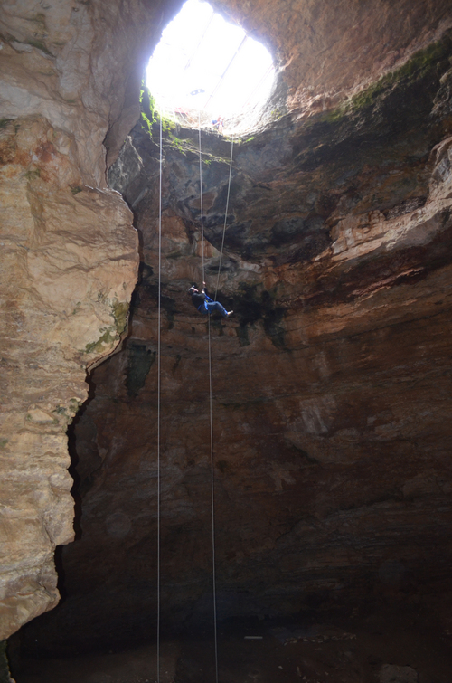 This July 2014 image provided by the Bureau of Land Management shows Justin Sipla ascending up a rope 80 feet after working at the bottom of the Natural Trap Cave in north-central Wyoming. The cave holds the remains of tens of thousands of animals, including many now-extinct species, from the late Pleistocene period tens of thousands of years ago. Scientists have resumed digging for the first time in more than 30 years. (AP Photo/Bureau of Land Management)