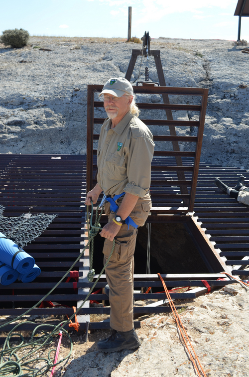 This July 2014 image provided by the Bureau of Land Management shows BLM Paleontologist Brent Breithaupt at the mouth to the interior of the Natural Trap Cave in north-central Wyoming. The cave holds the remains of tens of thousands of animals, including many now-extinct species, from the late Pleistocene period tens of thousands of years ago. Scientists have resumed digging for the first time in more than 30 years. (AP Photo/Bureau of Land Management)