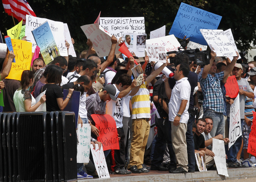 Protesters ask for help for Yazidi people who are stranded by violence in northern Iraq, Thursday, Aug. 7, 2014, across from the White House in Washington. The Obama administration is weighing an urgent response to help trapped religious minorities in Iraq, with one option being delivery of humanitarian aid. (AP Photo/Jacquelyn Martin)