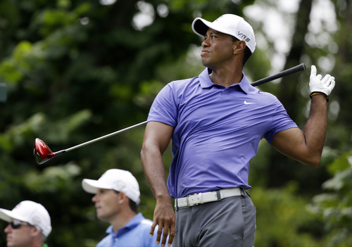 Tiger Woods reacts to a poor tee shot on the seventh hole during the first round of the PGA Championship golf tournament at Valhalla Golf Club on Thursday, Aug. 7, 2014, in Louisville, Ky. (AP Photo/John Locher)