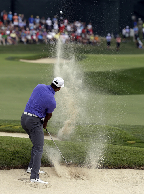 Tiger Woods hits out of the bunker on the 18th hole during the first round of the PGA Championship golf tournament at Valhalla Golf Club on Thursday, Aug. 7, 2014, in Louisville, Ky. (AP Photo/John Locher)
