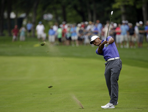 Tiger Woods hits from the fairway on the 16th hole during the first round of the PGA Championship golf tournament at Valhalla Golf Club on Thursday, Aug. 7, 2014, in Louisville, Ky. (AP Photo/John Locher)