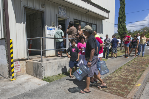 People line up at the Menehune Water Company to purchase cases of water and fill up water jugs in Aiea, Hawaii on Thursday, Aug. 7, 2014. With Hurricanes Iselle and Julio approaching, bottles of water are disappearing off shelves in Hawaii prompting many to line up for several hours to purchase water directly from the company. (AP Photo/Marco Garcia)