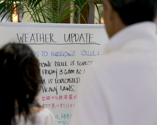 A couple reads a weather update written on a white board in the lobby of a hotel in Waikiki in Honolulu on Thursday, Aug. 7, 2014. With Iselle, Hawaii is expected to take its first direct hurricane hit in 22 years. Tracking close behind it is Hurricane Julio. (AP Photo/Marco Garcia)