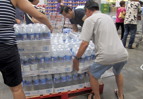 Shoppers lift cases of bottled water in preparation for a hurricane and tropical storm heading toward Hawaii at the Iwilei Costco in Honolulu on Tuesday, Aug. 5, 2014. Two big storms so close together is rare in the eastern Pacific. Hurricane Iselle could make landfall by Friday and Tropical Storm Julio could hit two or three days later, weather officials said. (AP Photo/Audrey McAvoy)