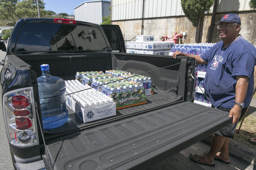 Honolulu resident Stan Nuuhiwa fills his truck with cases of water from the Menehune Water Company, Thursday, Aug. 7, 2014, in Aiea, Hawaii.  Hawaii is bracing for two back to back hurricanes, Iselle and Julio, which are on course to hit the Islands.  Bottles of water are quickly disappearing off shelves in Hawaii causing many people to line up for several hours to purchase water directly from the company.  (AP Photo/Marco Garcia)
