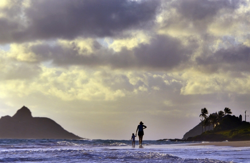 Anne Kllingshirn of Kailua, Hawaii walks with her daughter Emma, 1, as storm clouds are are seen during the sunrise hours on Kailua Beach, in Kailua, Hawaii, Thursday morning Aug. 7, 2014 . Hurricane Iselle is expected to arrive on the Big Island on Thursday evening, bringing heavy rains, winds gusting up to 85 mph and flooding in some areas. Weather officials changed their outlook on the system Wednesday after seeing it get a little stronger, giving it enough oomph to stay a hurricane as it reaches landfall. (AP Photo/Luci Pemoni)