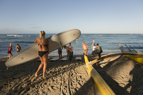 A group of tourists from California head into the water for a surf lesson in Waikiki in Honolulu on Thursday, Aug. 7, 2014. With Iselle, Hawaii is expected to take its first direct hurricane hit in 22 years. Tracking close behind it is Hurricane Julio. (AP Photo/Marco Garcia)