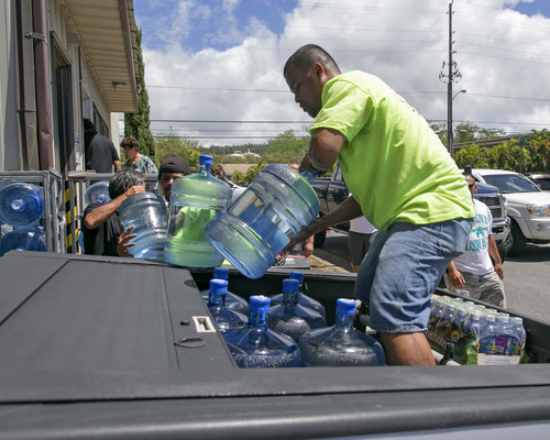 Workers at the Menehune Water Company load five gallon bottles of water into a customer's truck, Thursday, Aug. 7, 2014, in Aiea, Hawaii.  Hawaii is bracing for two back to back hurricanes, Iselle and Julio, which are on course to hit the Islands.  Bottles of water are quickly disappearing off shelves in Hawaii causing many people to line up for several hours to purchase water directly from the company.  (AP Photo/Marco Garcia)