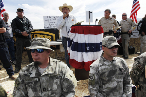File - In this April 12, 2014 file photo, rancher Cliven Bundy, center, addresses his supporters along side Clark County Sheriff Doug Gillespie, right, while being guarded by self-described militia members in the foreground. The 34-year-old son of the Nevada rancher who hosted armed protesters against federal agents in a cattle roundup dispute in April is facing arrest in a separate case stemming from his felony conviction on 2012 burglary and weapon charges. Cliven Lance Bundy, not seen, said Monday, July 14, 2014, he knows he's named in a contempt-of-court warrant issued July 8 for failing to appear before a Clark County District Court judge overseeing a drug diversion program in Las Vegas. (AP Photo/Las Vegas Review-Journal, Jason Bean, File)