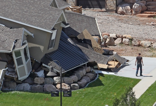 A man looks at a home destroyed by a landslide in a hillside community of North Salt Lake, Utah, Tuesday, Aug. 5, 2014. One home was destroyed and 27 others were evacuated after a landslide early Tuesday struck an upscale suburban Salt Lake City community, where officials had worried for nearly a year about cracked soil on the hillside above the houses. (AP Photo/Rick Bowmer)