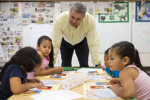 ADVANCE FOR SUNDAY, AUG. 10 AND THEREAFTER - This photo taken July 21, 2014 shows Kennett Consolidated School District Superintendent Barry Tomasetti meeting with young students in teacher Jane Cornell's summer school class at Mary D. Lang Kindergarten Center in Kennett Square, Pa. For the first time ever _ U.S. public schools are projected this fall to have more minority students enrolled than white, a shift largely fueled by growth in the numbers of Hispanic children. White students are still expected to be the largest racial group in the public schools this year at 49.8 percent, but according to the National Center for Education Statistics, minority students, when added together, will now make up the majority. (AP Photo/Matt Rourke)