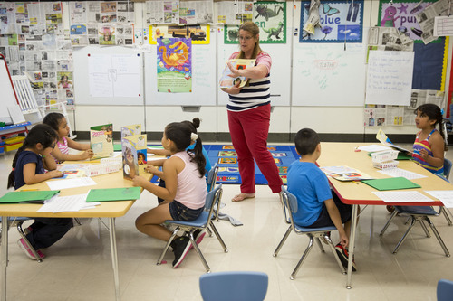 ADVANCE FOR SUNDAY, AUG. 10, 2014 - This photo taken July 21, 2014 shows  teacher Jane Cornell working with young students on their storytelling skills during summer school at Mary D. Lang Kindergarten Center in Kennett Square, Pa. For the first time ever _ U.S. public schools are projected this fall to have more minority students enrolled than white, a shift largely fueled by growth in the numbers of Hispanic children. White students are still expected to be the largest racial group in the public schools this year at 49.8 percent, but according to the National Center for Education Statistics, minority students, when added together, will now make up the majority. (AP Photo/Matt Rourke)