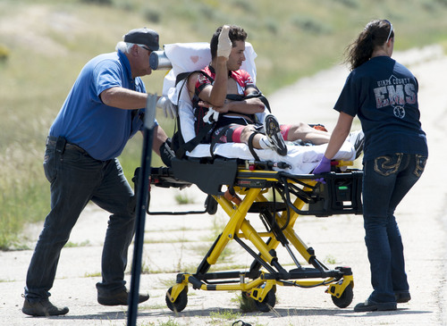 Steve Griffin  |  The Salt Lake Tribune   A battered and bloodied Gregory Brenes is pushed toward a waiting ambulacne by Uinta County emergency personal after crashing  as Tour of Utah riders raced along State Road 150 outside of Evanston, Wyoming during the fifth stage of the event Friday, August 8, 2014. Riders road between Evanston and Kamas  two gateway cities to the High Uintas Wilderness and beautiful Mirror Lake Scenic Byway.