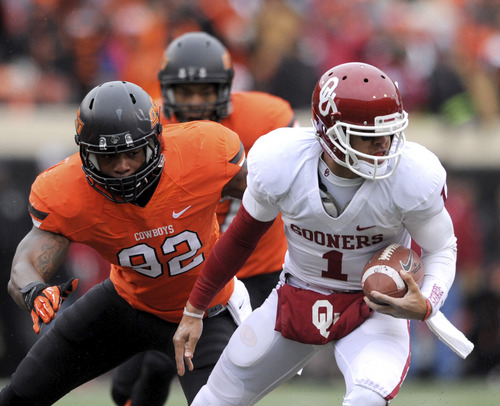 Oklahoma State defensive end Jimmy Bean, left, reaches for Oklahoma quarterback Kendal Thompson during the first half of an NCAA football game in Stillwater, Okla., Saturday, Dec. 7, 2013. Thompson had 17 yards passing in the 33-24 win over rival Oklahoma State. (AP Photo/Brody Schmidt)