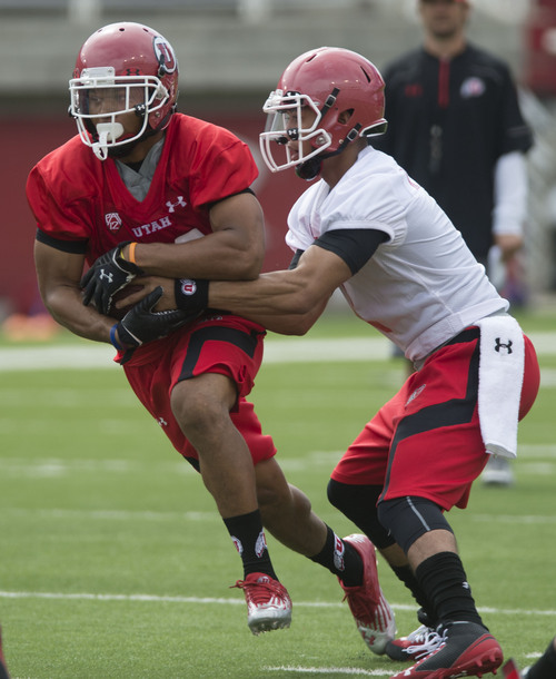 Steve Griffin  |  The Salt Lake Tribune   Utah running back Devontae Booker takes a hand-off from quarterback Kendal Thompson during football practice at Rice Eccles Stadium in Salt Lake City, Utah Monday, August 4, 2014.