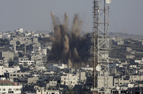 Smoke, dust and derbies rise after an Israeli strike in Gaza City in the northern Gaza Strip on Sunday, Aug. 10, 2014. (AP Photo/Adel Hana)