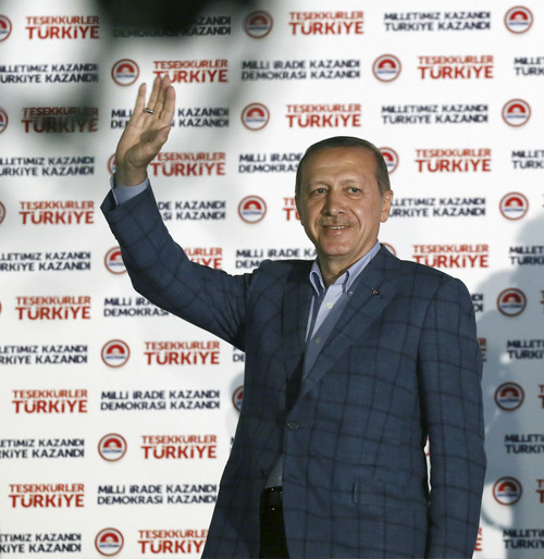 Turkish Prime Minister Recep Tayyip Erdogan acknowledges supporters after his election victory, in Ankara, Turkey, Sunday, Aug. 10, 2014. Erdogan won Turkey's first direct presidential election Sunday, striking a conciliatory tone toward critics who fear he is bent on a power grab as he embarks on another five years at the country's helm.(AP Photo/Burhan Ozbilici)