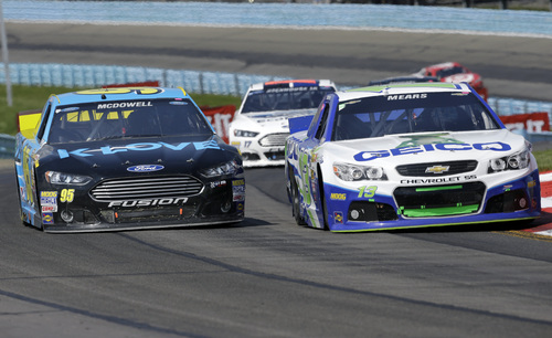 Michael McDowell (95) and Casey Mears (13) battle for position in the esses during a NASCAR Sprint Cup Series auto race at Watkins Glen International, Sunday, Aug. 10, 2014, in Watkins Glen, N.Y. (AP Photo/Mel Evans)