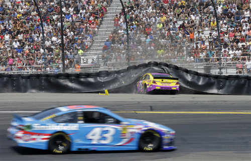 Aric Almirola (43) drives through Turn 1 as Cole Whitt (26) crashes into the tire wall during a NASCAR Sprint Cup Series auto race at Watkins Glen International, Sunday, Aug. 10, 2014, in Watkins Glen, N.Y. (AP Photo/Mel Evans)