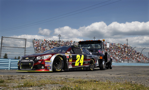 Jeff Gordon's  (24) is pushed back to the pits during a NASCAR Sprint Cup Series auto race at Watkins Glen International, Sunday, Aug. 10, 2014, in Watkins Glen N.Y. (AP Photo/Mel Evans)