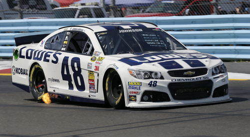 Flames shoot from the exhaust of Jimmie Johnson's race car (48) during a NASCAR Sprint Cup Series auto race at Watkins Glen International, Sunday, Aug. 10, 2014, in Watkins Glen N.Y. (AP Photo/Mel Evans)