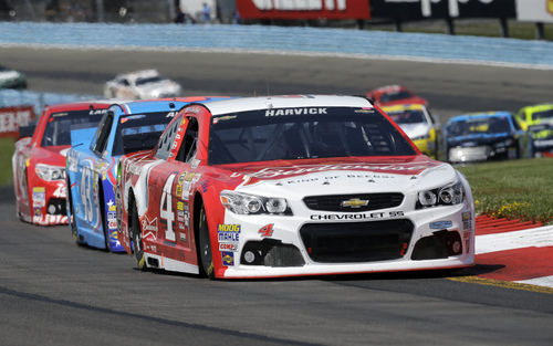 Kevin Harvick (4) leads a group of racers through the esses during a NASCAR Sprint Cup Series auto race at Watkins Glen International, Sunday, Aug. 10, 2014, in Watkins Glen N.Y. (AP Photo/Mel Evans)