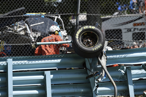 Wreckage from the race car of Michael McDowell (95) protrudes through the catch fence during a NASCAR Sprint Cup Series auto race at Watkins Glen International, Sunday, Aug. 10, 2014, in Watkins Glen N.Y. The crash and resulting damage to the protective barriers resulted in race stoppage for over an hour. (AP Photo/Derik Hamilton)
