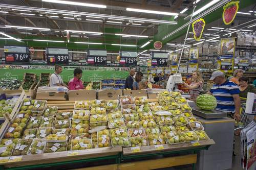 Customers look at shelves with imported fruit and vegetables at a supermarket in Novosibirsk, about 2,800 kilometers (1,750 miles) east of Moscow, Russia, Thursday, Aug. 7, 2014. Russia banned most food imports from the West on Thursday in retaliation for sanctions over Ukraine, an unexpectedly sweeping move that will cost farmers in North America, Europe and Australia billions of dollars but will also likely lead to empty shelves in Russian cities. (AP Photo/Ilnar Salakhiev)
